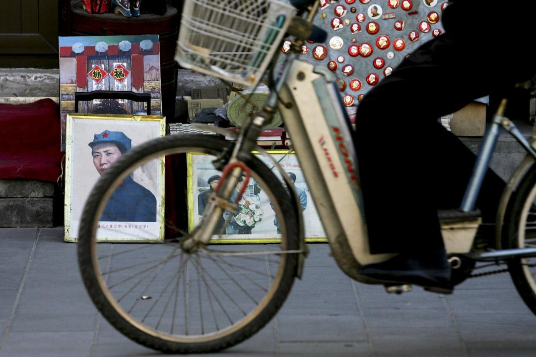 2007年1 16日,北京的彩釉街,一名騎單車的人經過已故領導人毛澤東的徽章和肖像。 攝:Guang Niu/Getty Images