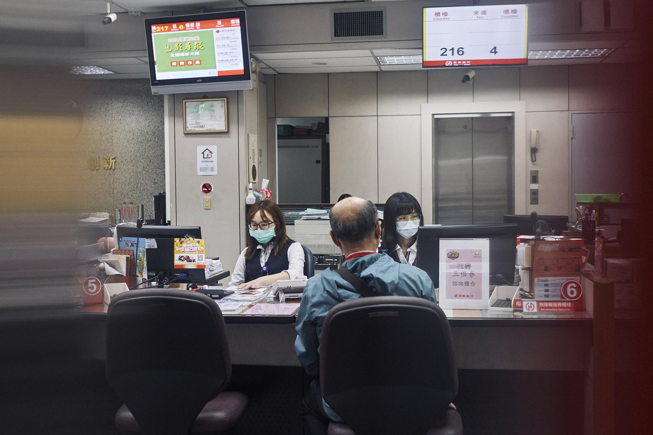 2020年12月2日台灣台北,銀行櫃員戴著口罩為客戶提供服務。