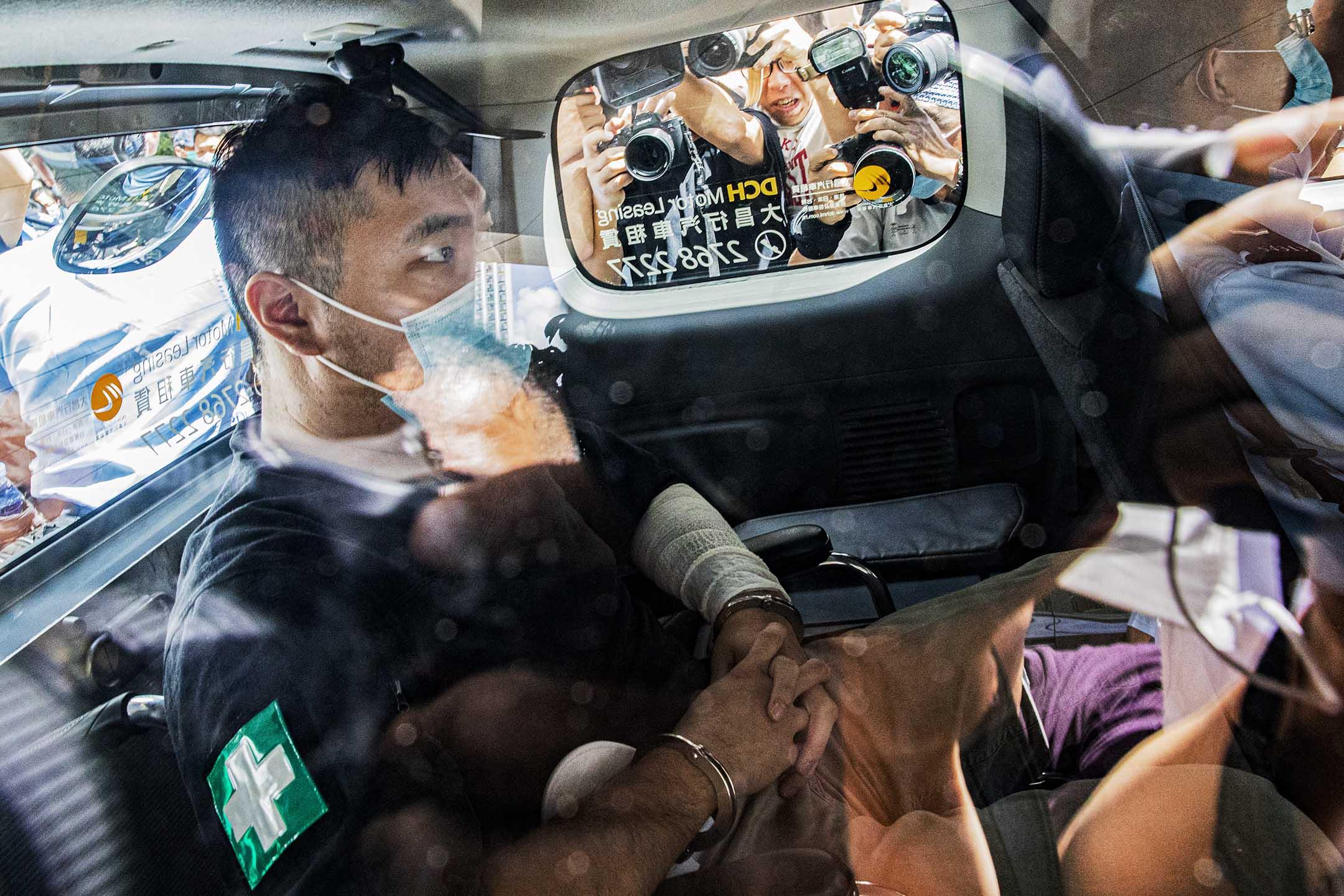 2020年7月6日,香港西九龍裁判法院,唐英傑被控駕駛插上「光復香港 時代革命」旗幟的電單車撞向警察,被指違反《國安法》由警車押送至法院提堂。 攝:陳焯煇/端傳媒