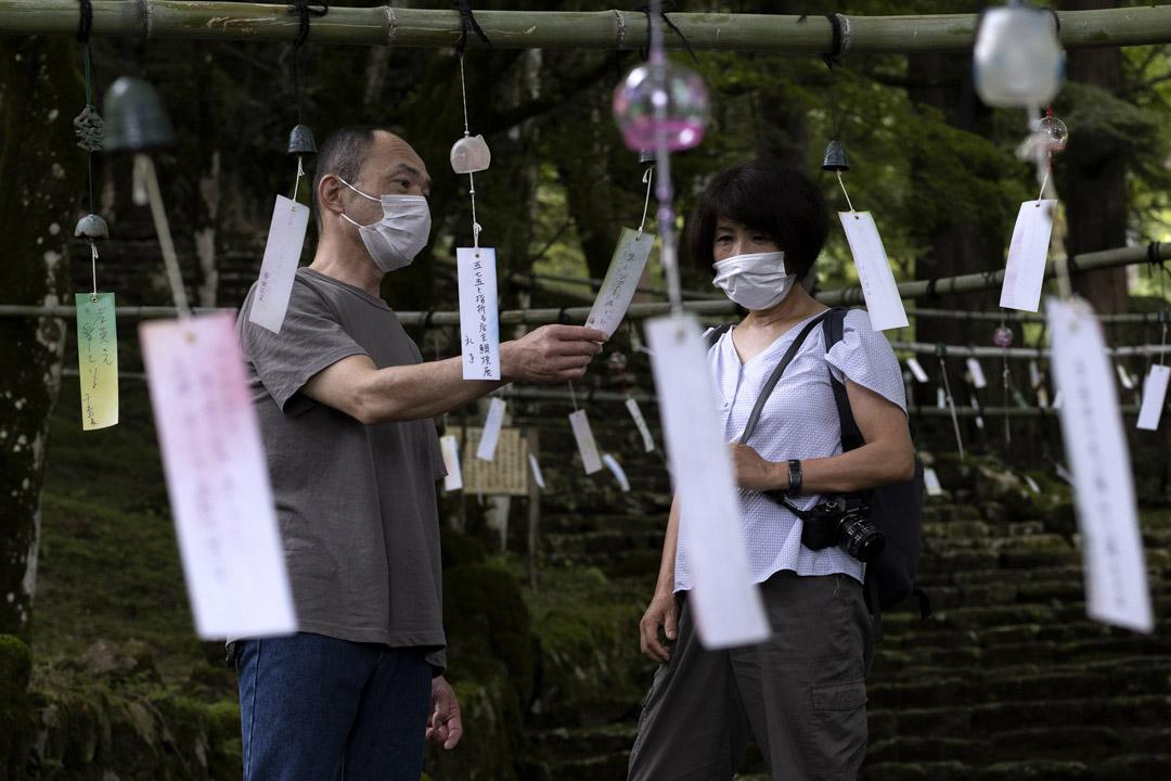 2021年7月13日,丹波一名戴著口罩的市民在青垣寺閲讀印有人們願望的風鈴紙條。