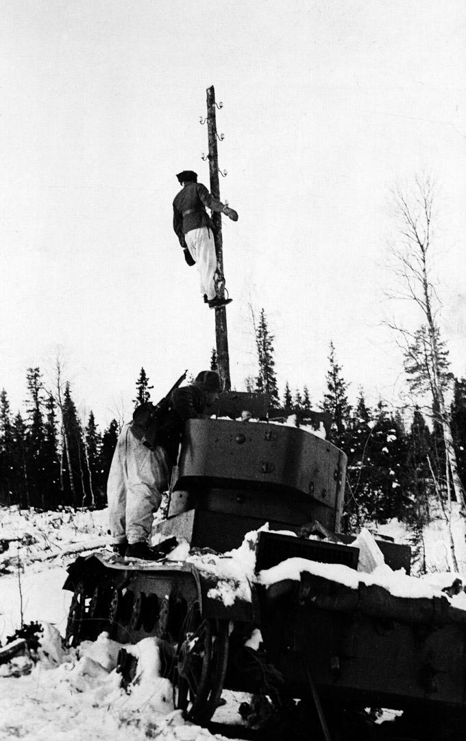1939年,冬季戰爭中的芬蘭士兵正在修理傳輸線,前景是一輛被摧毀的蘇聯坦克。