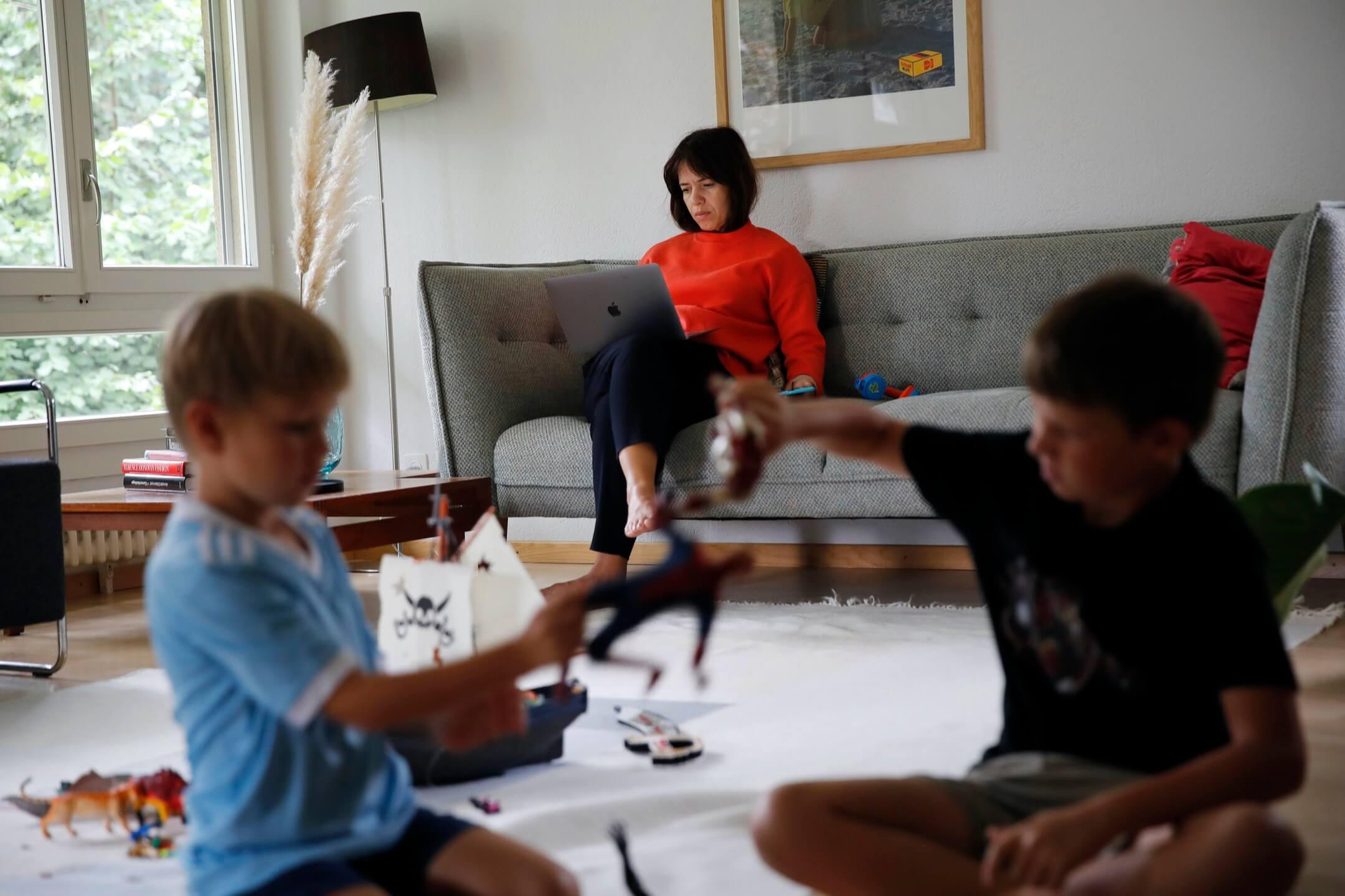 2020年8月19日,瑞士伯恩,一位媽媽因疫情關係需要在家工作,她的一對兒子在大廳玩耍。 攝:Stefan Wermuth/Bloomberg via Getty Images