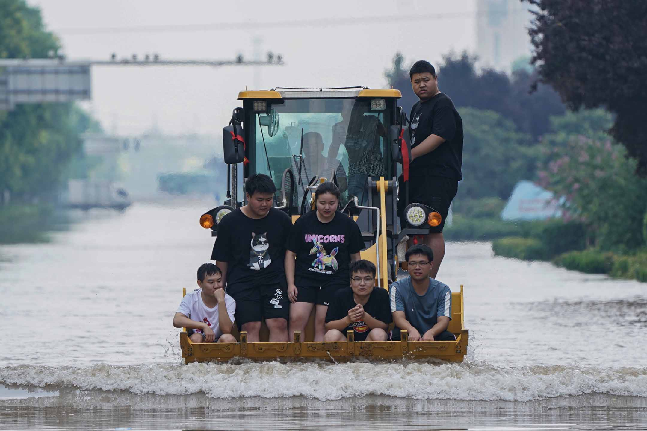 2021年7月24日中國河南省新鄉市,救援人員使用裝載機疏散當地居民。
