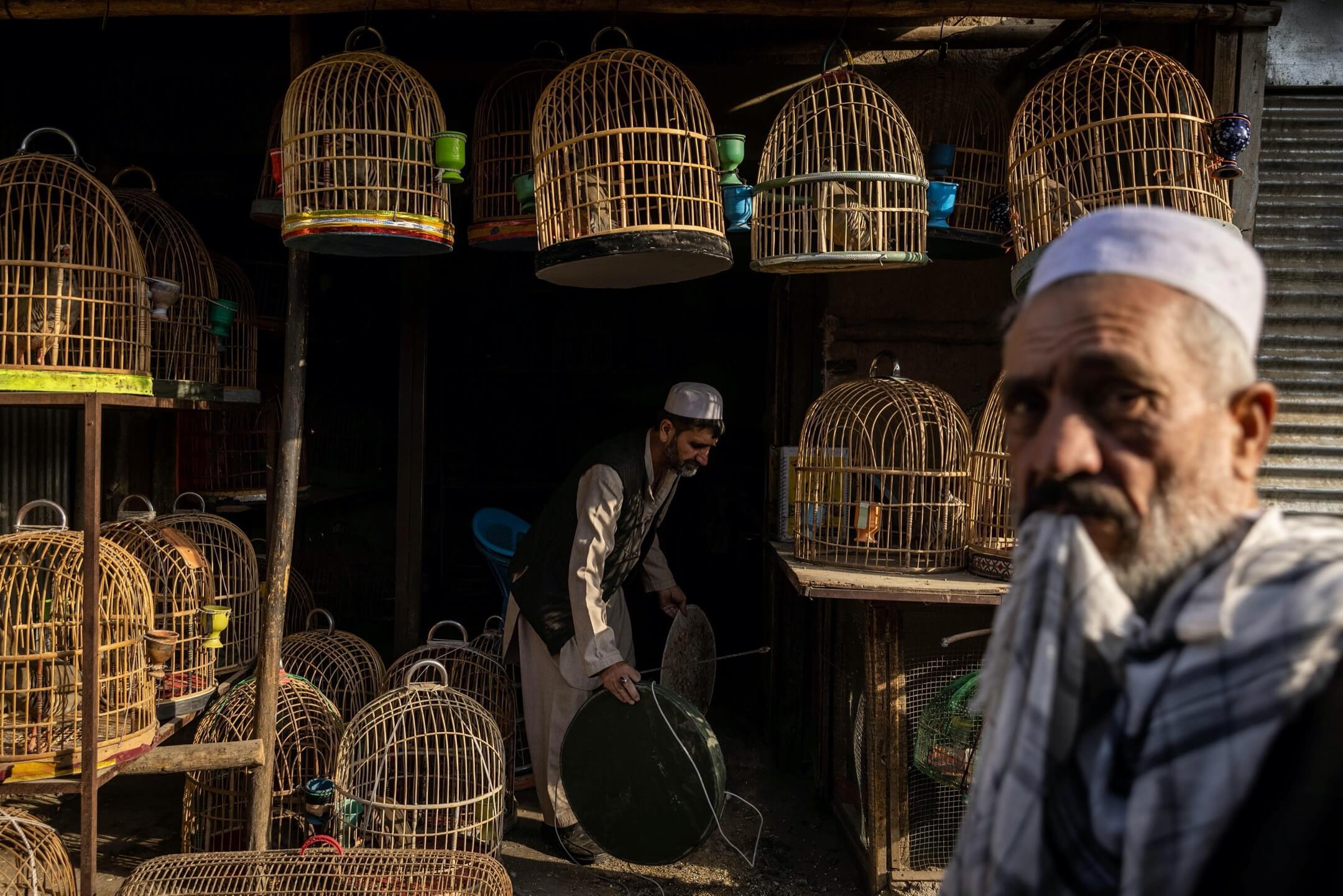 2021年7月4日,阿富汗喀布爾,一名賣鷓鴣的商人清洗店內的鳥籠。