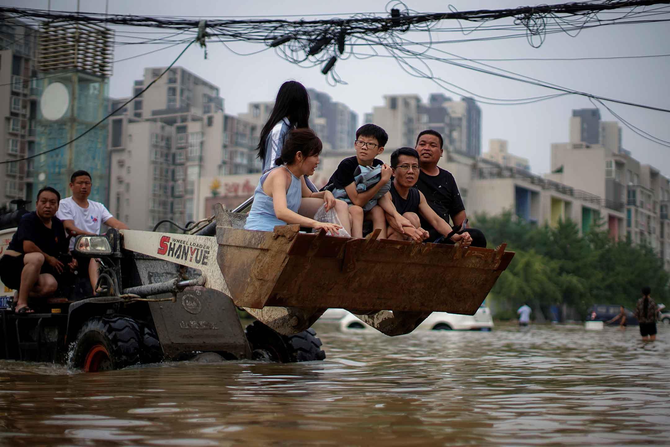2021年7月23日中國河南省鄭州市,人們騎著裝載機穿過洪水淹没的街道。 攝:Aly Song/Reuters/達志影像