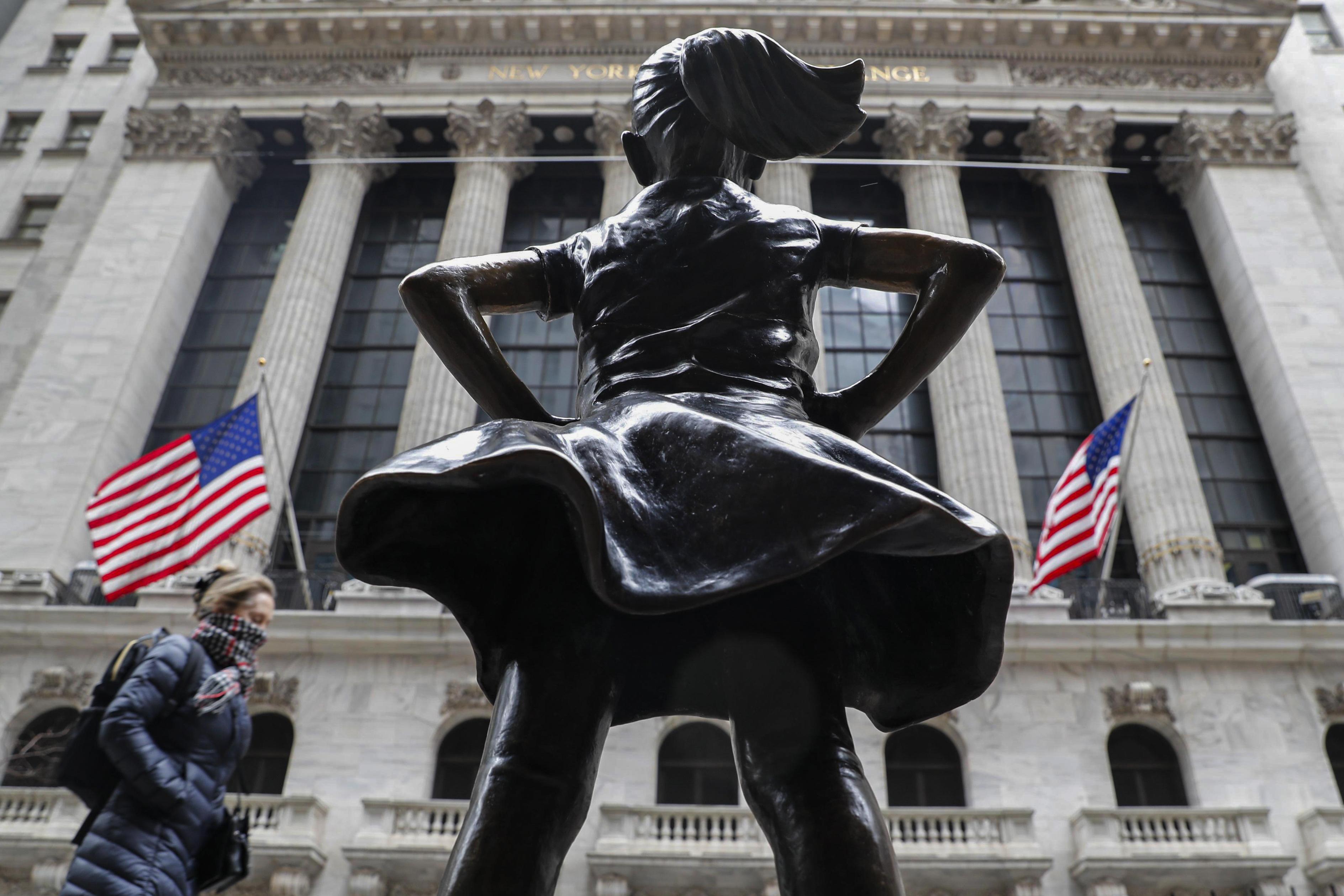 2020年3月12日紐約,一名戴著圍巾的行人在紐約證券交易所 (NYSE) 和無畏女孩雕像旁散步。