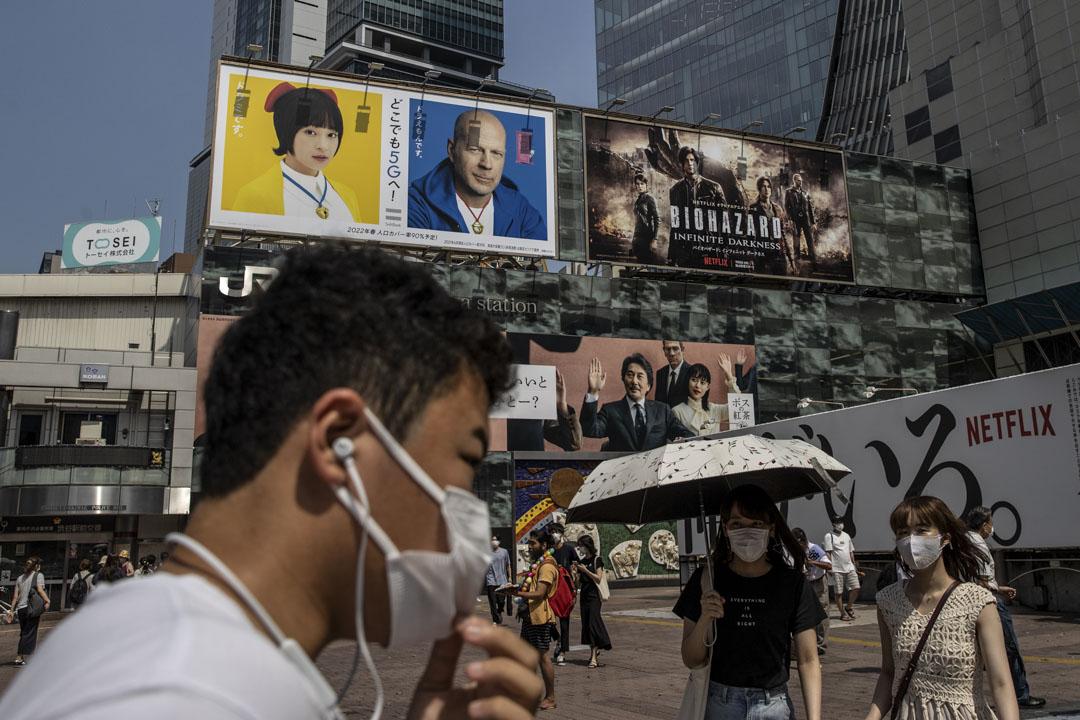 2021年7月12日日本東京,戴著口罩的人們走過澀谷站, 由於距離奧運會開幕還不到兩週,日本政府試圖遏制2019冠狀病毒死灰復燃。 攝:Takashi Aoyama/Getty Images