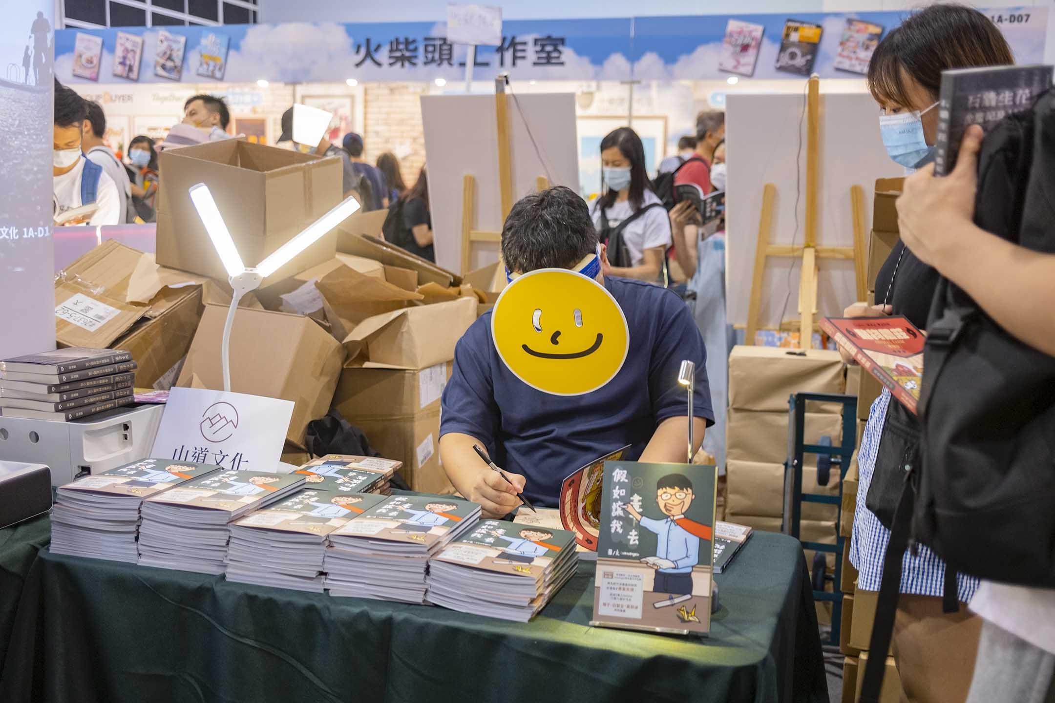 2021年7月18日香港書展,參展書商山道文化的攤檔,一名作者戴上臉具簽書。 攝:陳焯煇/端傳媒