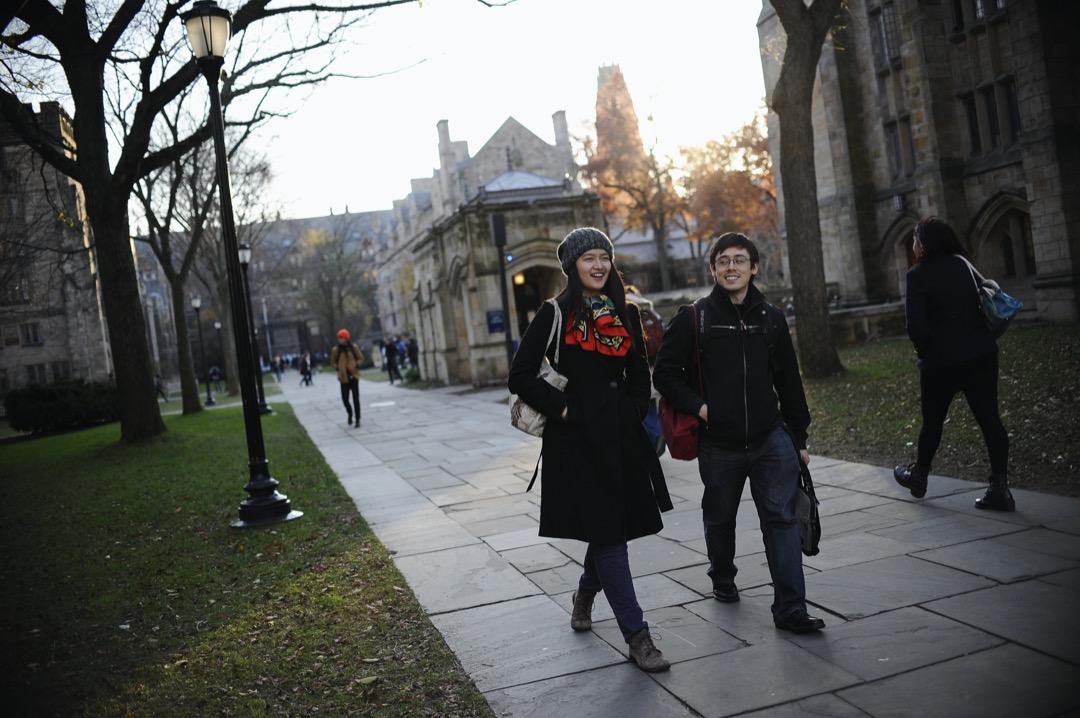 一位二年級中國留學生在美國耶魯大學與一位本地生同學散步。