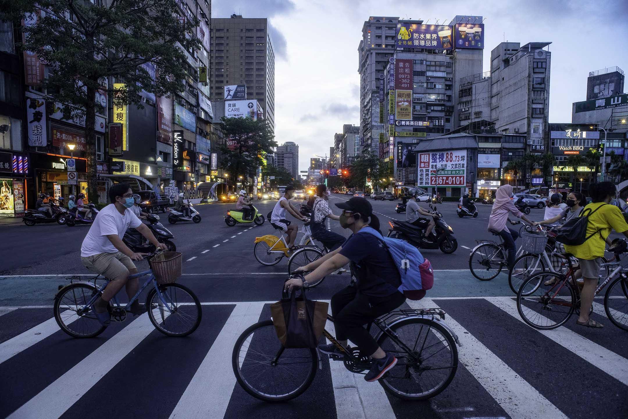 2021年7月20日台灣台北,人們騎著自行車橫過馬路。 攝:Shih Hsun Chao/LightRocket via Getty Images