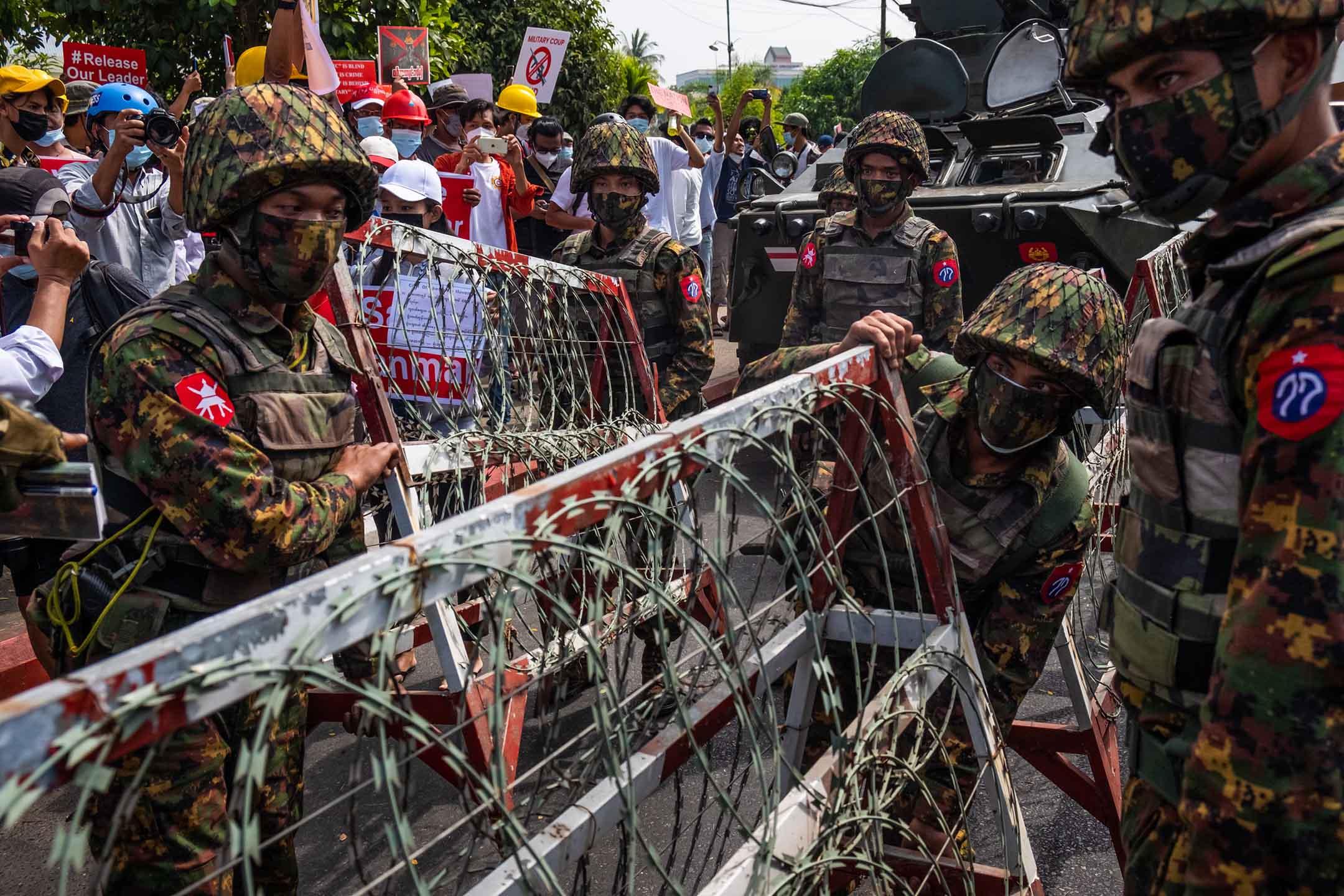 2021年2月15日緬甸仰光,示威者舉著橫幅並高喊口號,守衛中央銀行的緬甸軍人設置鐵絲網路障。
