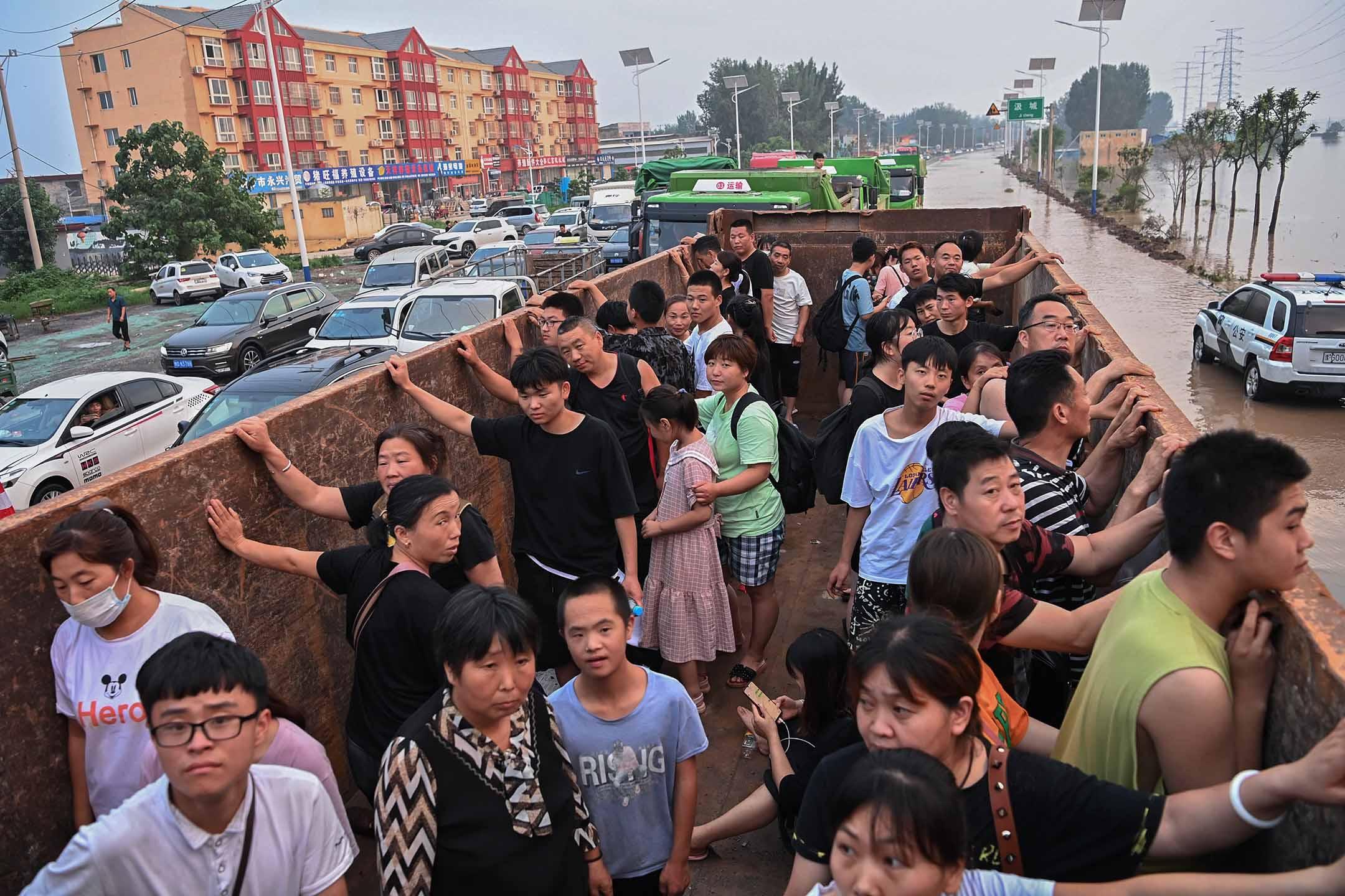 2021年7月23日中國河南省新鄉市 ,救援人員使用卡車從災區疏散當地居民。 攝:Cui Nan/China News Service via Getty Images