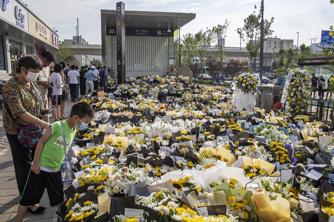 2021年7月21日在中國河南省鄭州市,有民眾在地鐵五號線沙口路站一個出口外獻花,悼念上週洪水倒灌之下在站內遇難的死者。 攝:Costfoto / Barcroft Media via Getty Images