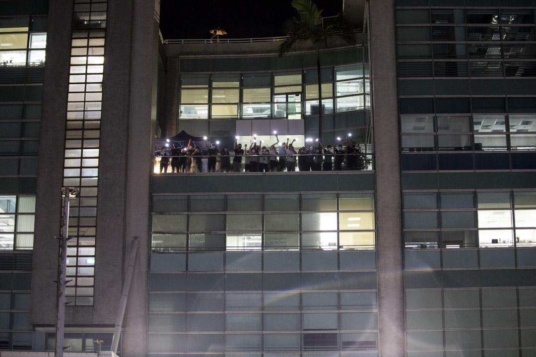 2021年6月23日,《蘋果日報》員工在大樓內揮動手機燈回應大樓外聲援的市民。