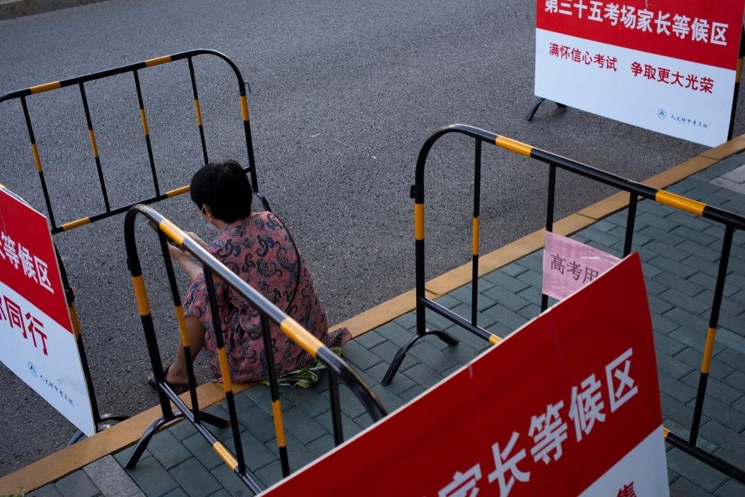 一位高考生的媽媽在考場外坐下,等候孩子完成考試。