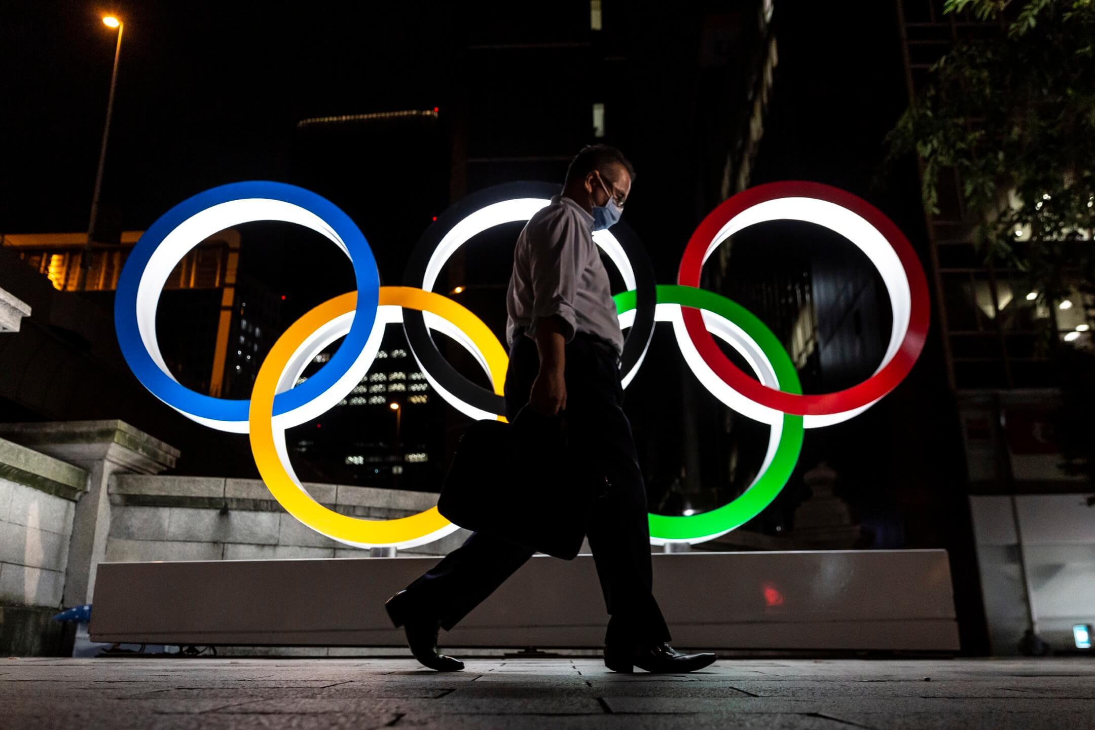 2021年7月20日,日本東京,一名戴著口罩的男子在市內一個奧運標誌前走過。 攝:Yuichi Yamazaki/Getty Images
