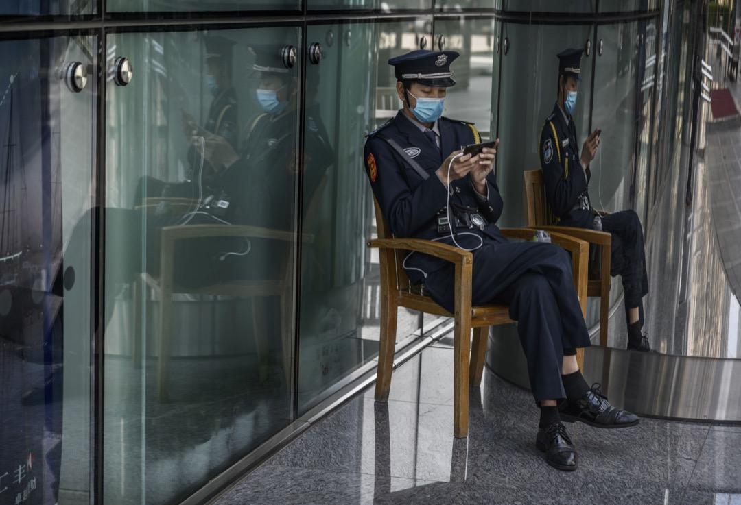 中國,一名保安員在辦公大樓外看手機。