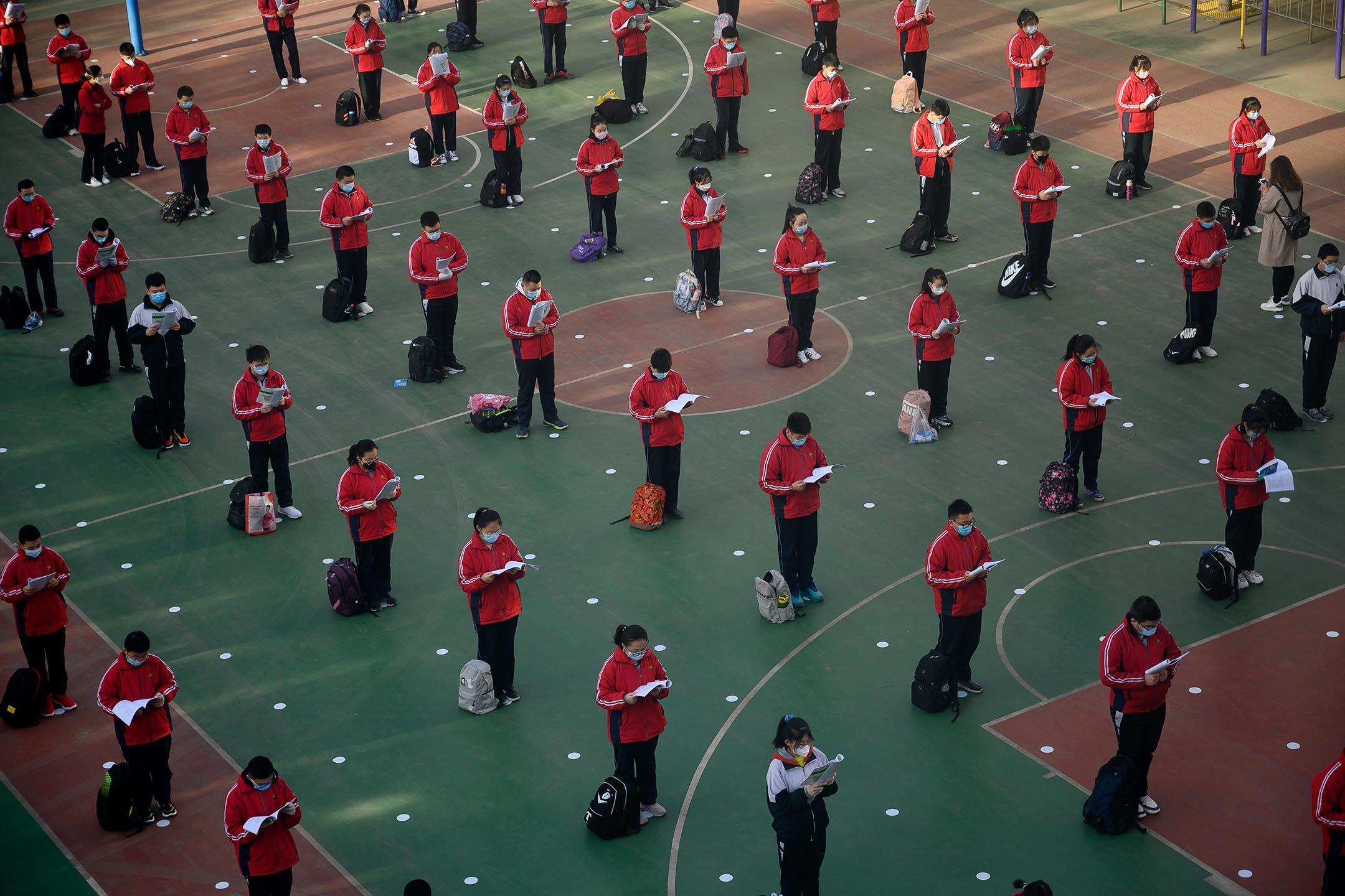 2020年4月25日中國太原,中學重新開放的第一天,戴著口罩的學生在操場上讀書。