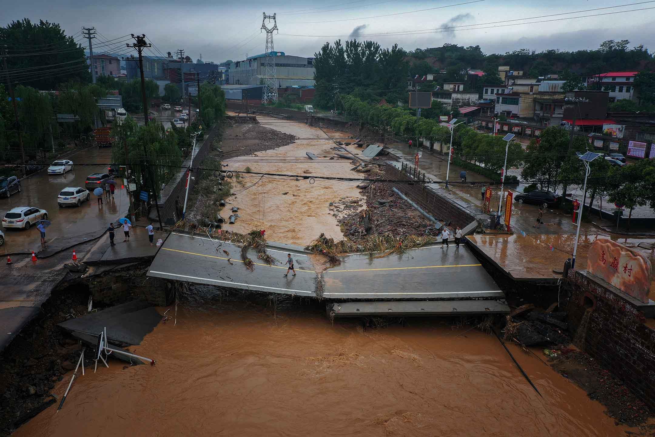 2021年7月21日中國河南省鞏義市,暴雨過後,人們走在受損的橋上。