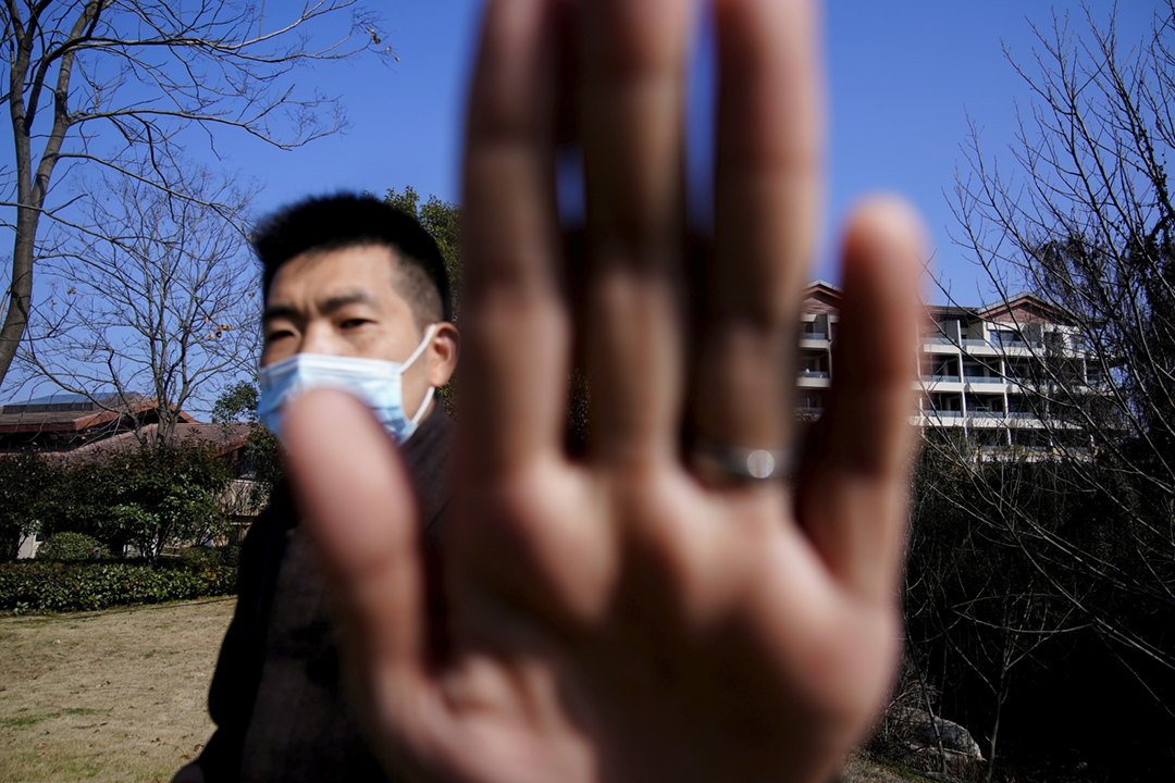 2021年2月6日在中國湖北省武漢市、受世界衛生組織委託赴華進行病毒溯源調查的國際專家組下塌的酒店外,一名中方保安人員用手遮擋記者的攝影鏡頭。 攝:Aly Song / Reuters