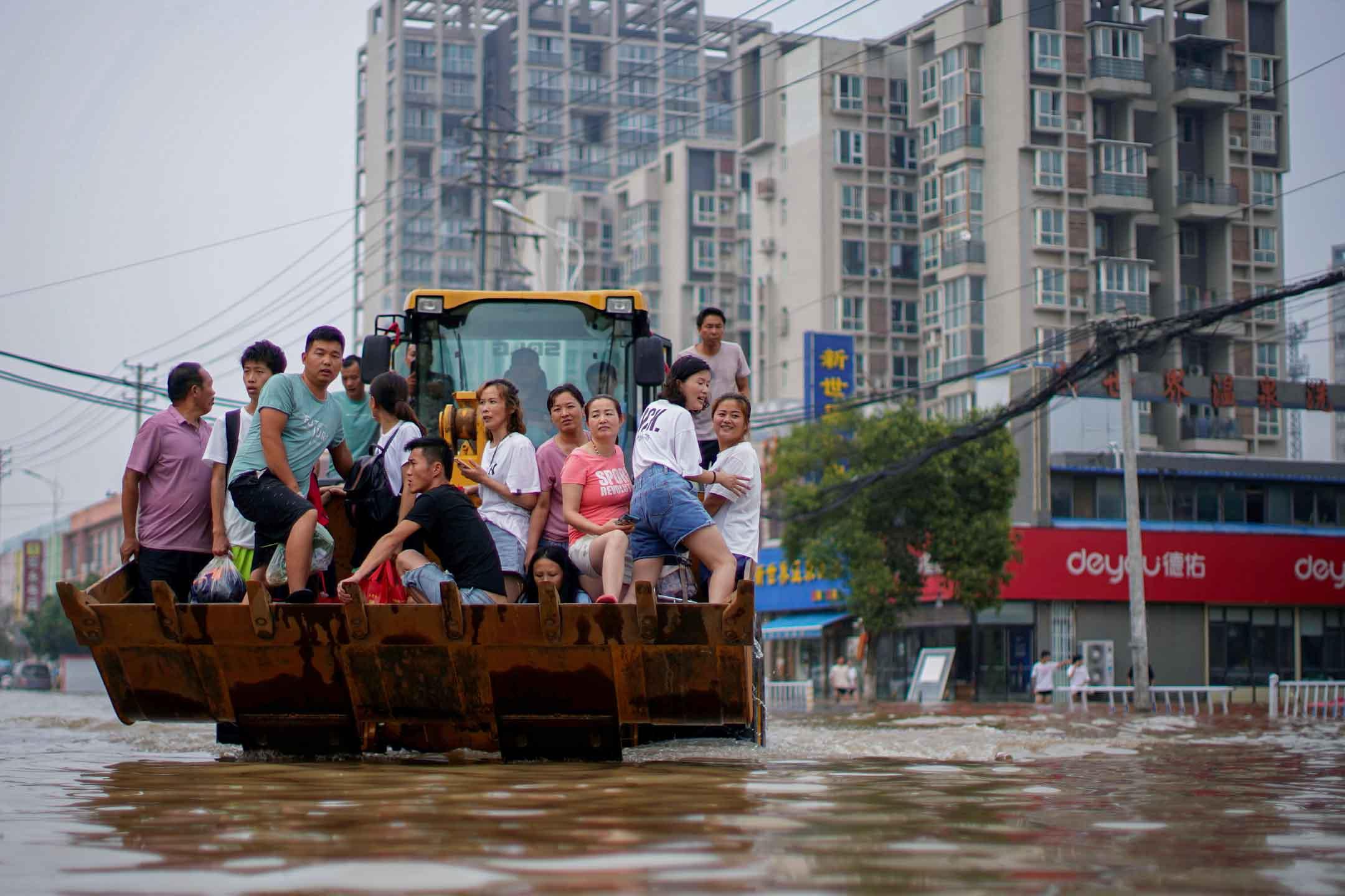 2021年7月23日中國河南省鄭州市,人們騎著裝載機穿過洪水。