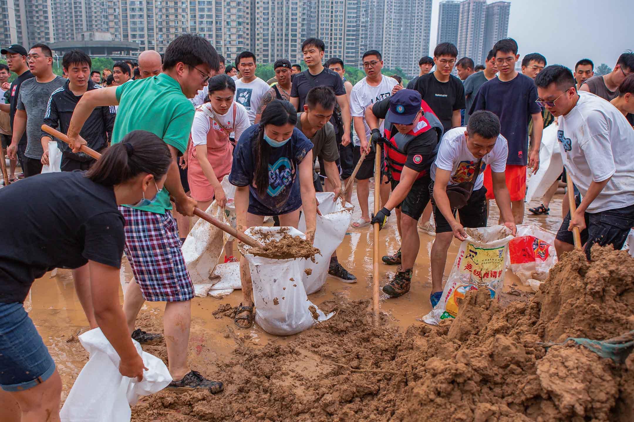2021年7月23日中國新鄉,救援隊和居民使用沙袋建造圍堰,防止暴雨後的洪水。