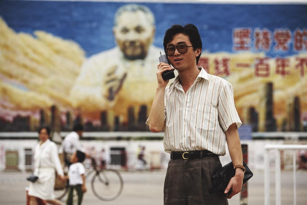 1993年,深圳一名男子正在使用手提電話,背後是鄧小平巨型室外宣傳畫。