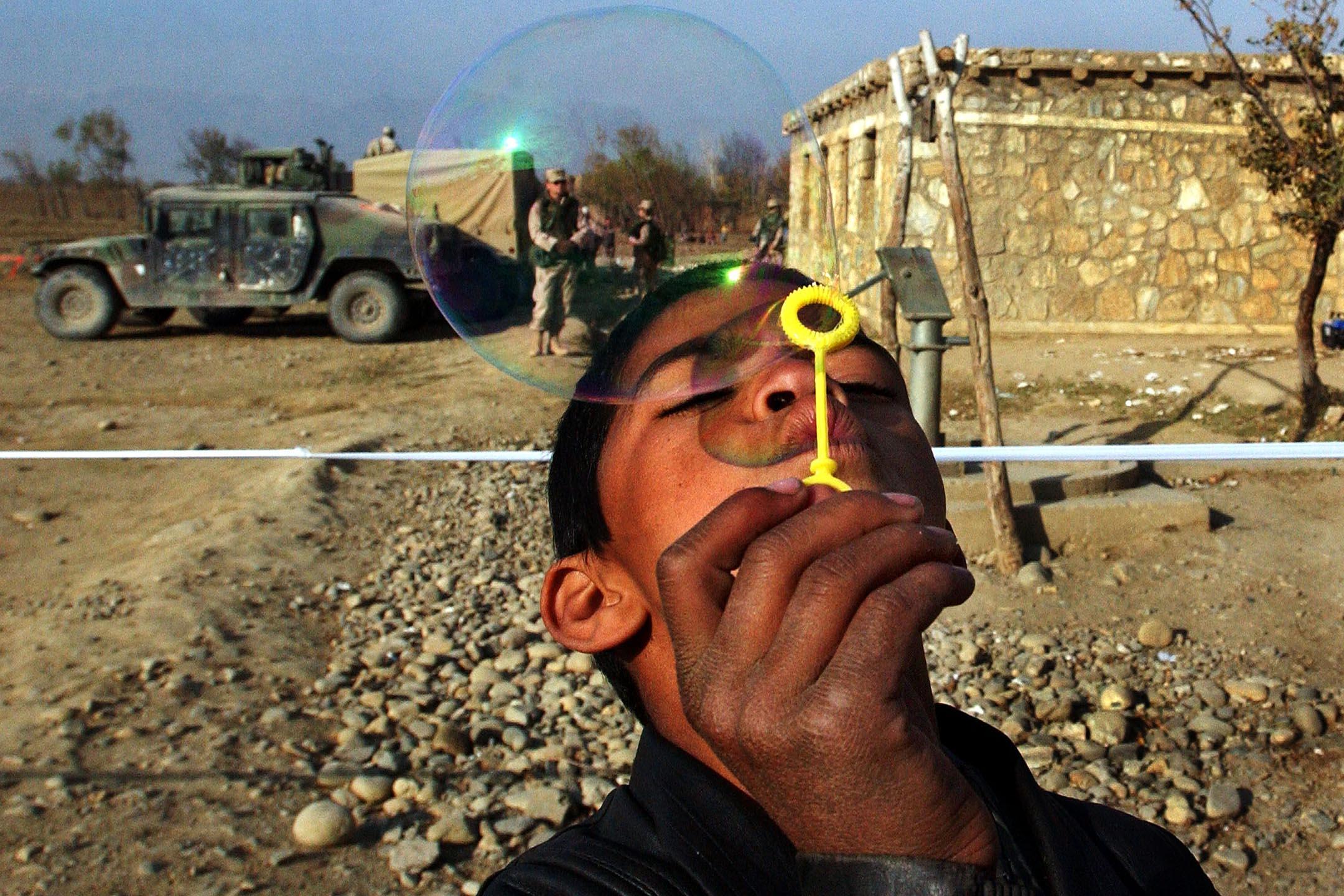 2002年12月3日阿富汗,一名阿富汗男孩吹著美國軍隊送給他的泡泡。