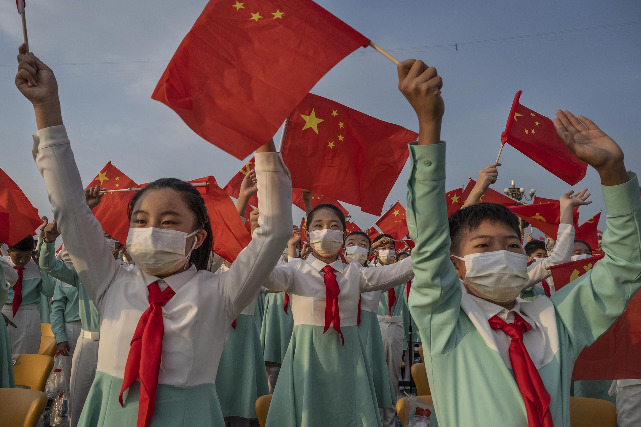 2021年7月1日中國北京,中國學生在天安門廣場舉行的慶祝共產黨成立 100 週年的儀式上揮舞黨旗和國旗。