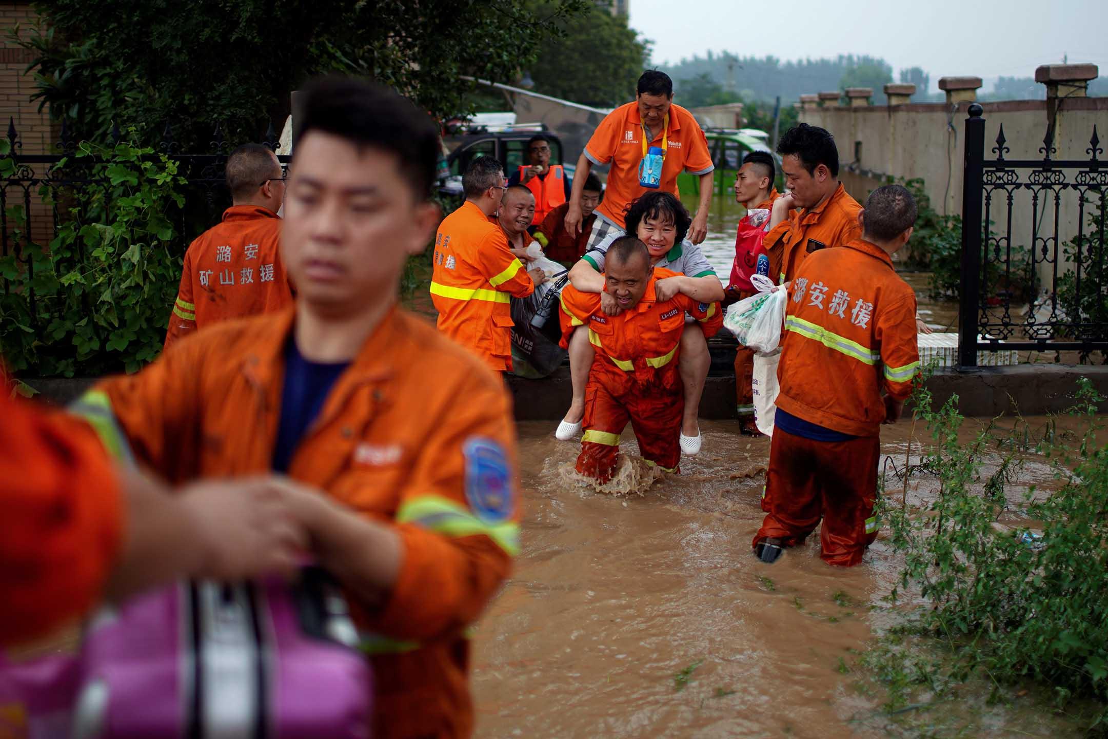 2021年7月23日中國河南省鄭州市,救援人員幫助被洪水困住的居民。 攝:Aly Song/Reuters/達志影像
