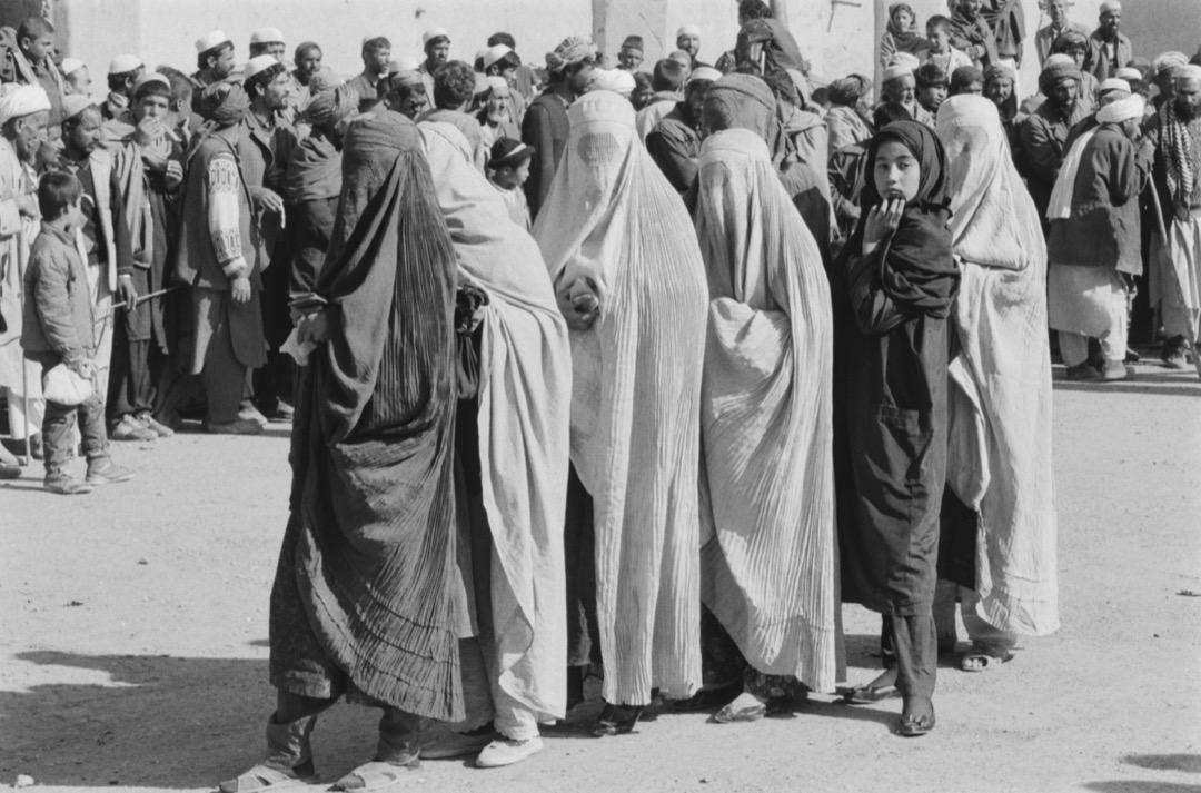 一群穿罩袍的女子站在阿富汗街頭。