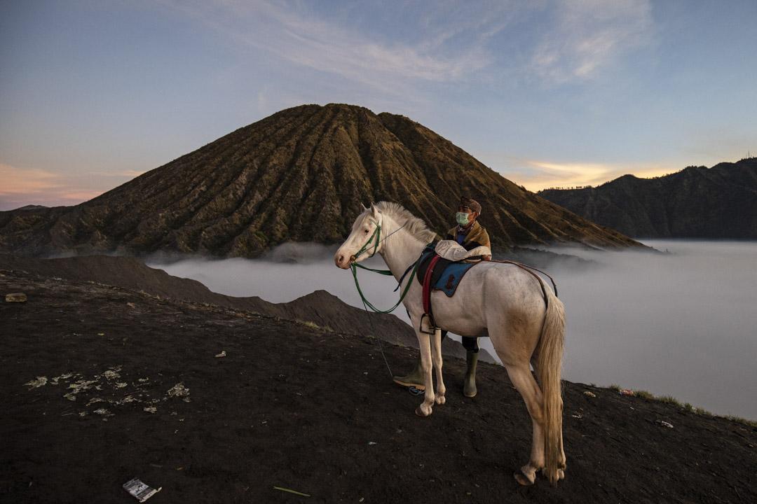 2021年6月26日,印尼爪哇普羅博林戈舉行的Yadnya Kasada 儀式期間,一名男子將一匹馬帶到巴托克山。