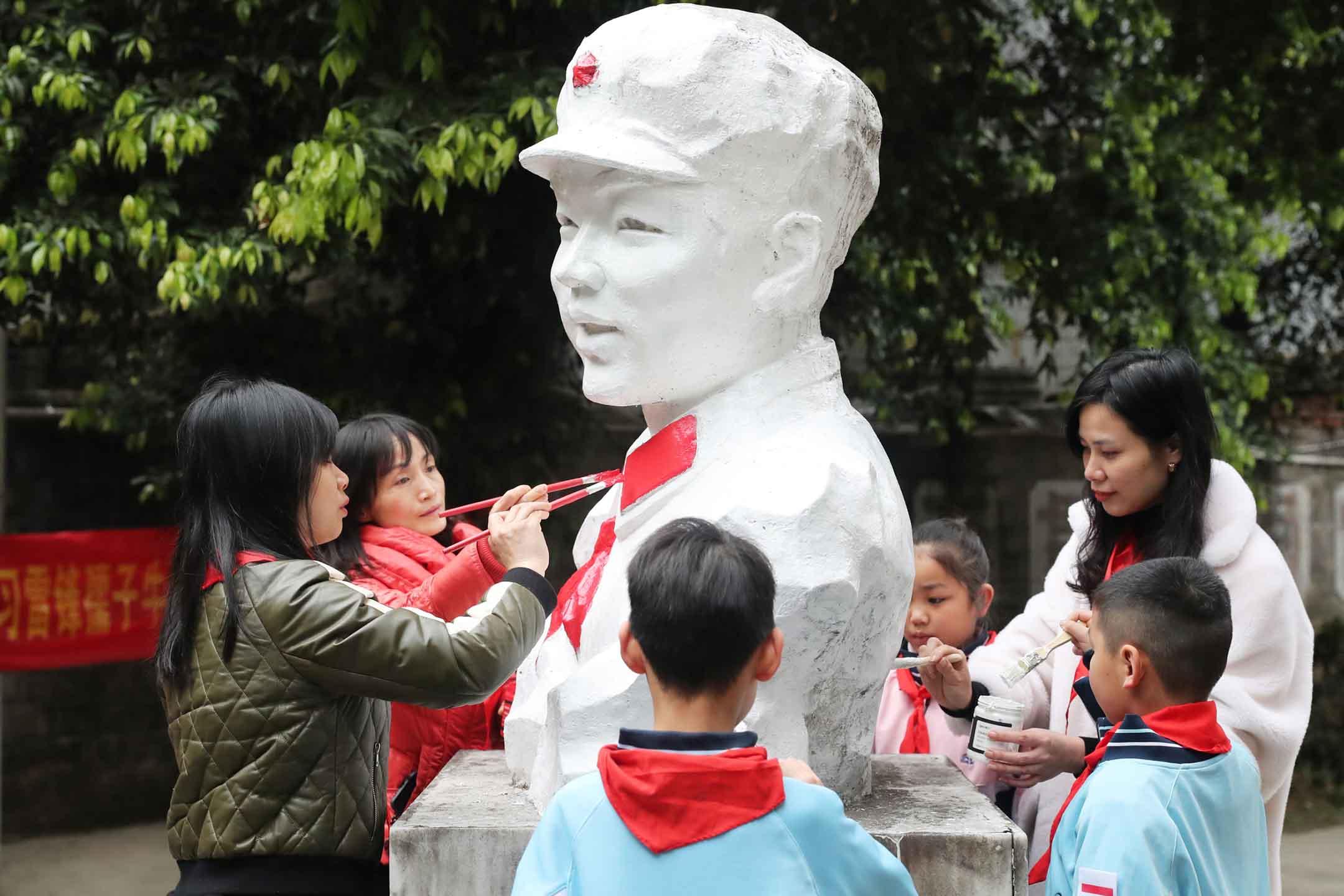 2021年3月2日中國桂林,學生們在「雷鋒日」為雷鋒雕像重新着色。