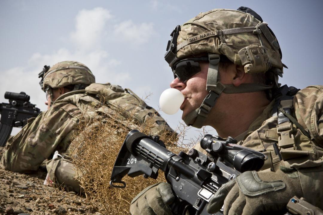 2013年2月3日,阿富汗南部坎大哈省,一名美軍士兵在哨站附近進行任務時嘴嚼吹波糖。