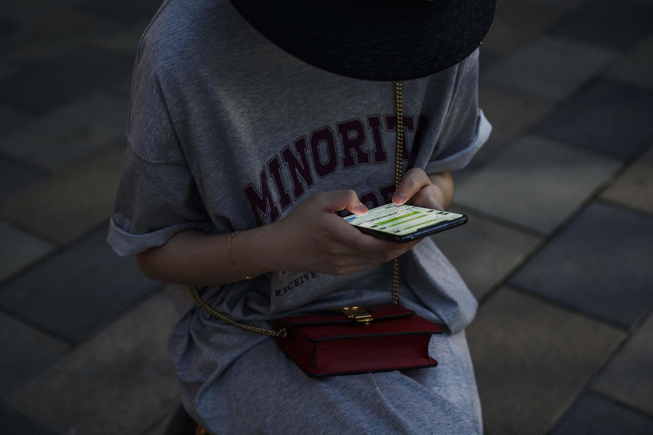 2020年8月14日中國北京,一位中國女性坐在中國北京的一個購物區,看著智能手機上的WeChat。