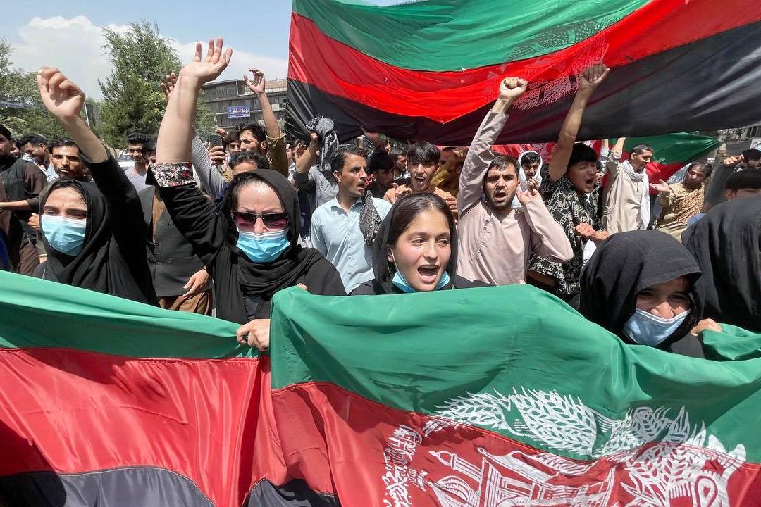 2021年8月19日,阿富汗喀布爾,獨立日集會遊行人群手舉國旗。 攝:Haroon Sabawoon/Getty Images