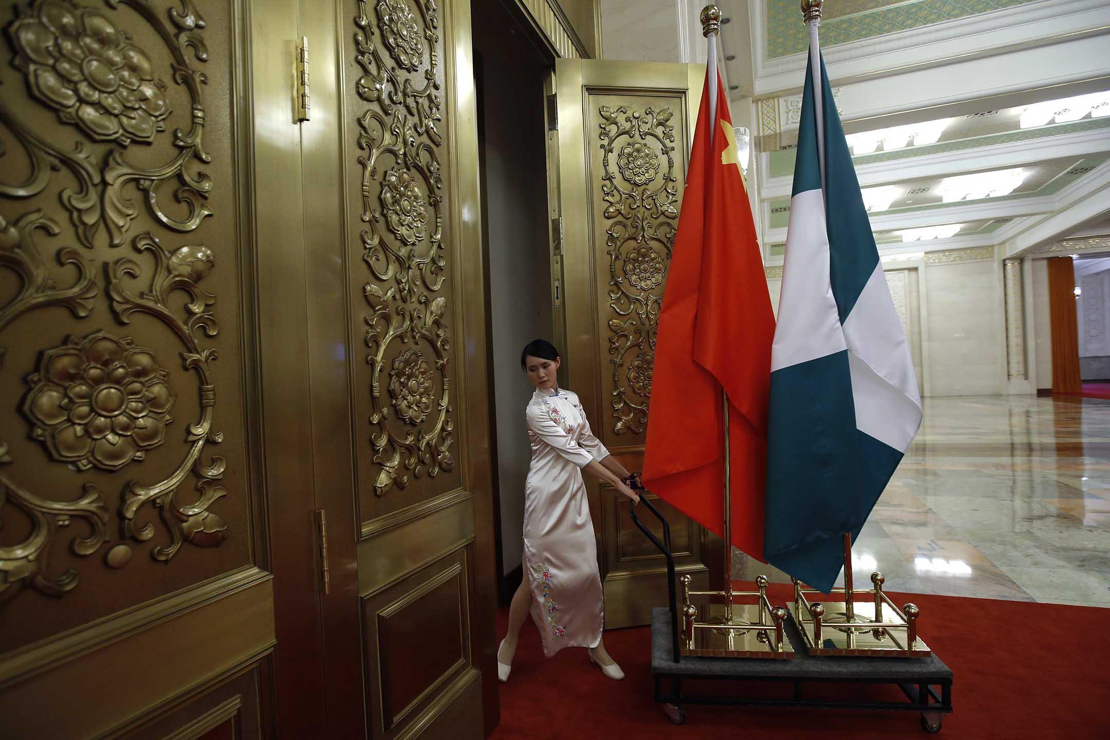 2013年7月10日北京人民大會堂,一名工作人員推著中國和尼日利亞國旗。