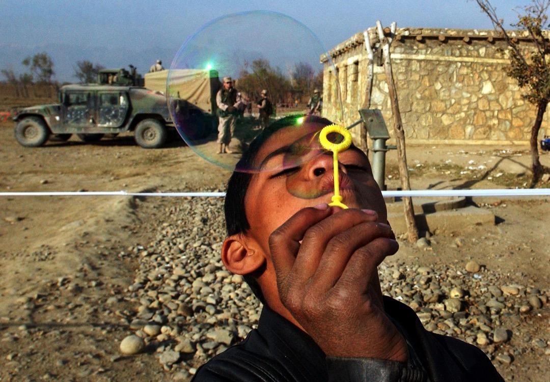 2002年12月3日,美軍到阿富汗中部小鎮Tadokhile進行人道支援任務,為當地逾百名村民提供免費醫療服務。一名男孩在玩耍由美軍部隊帶來的泡泡水。