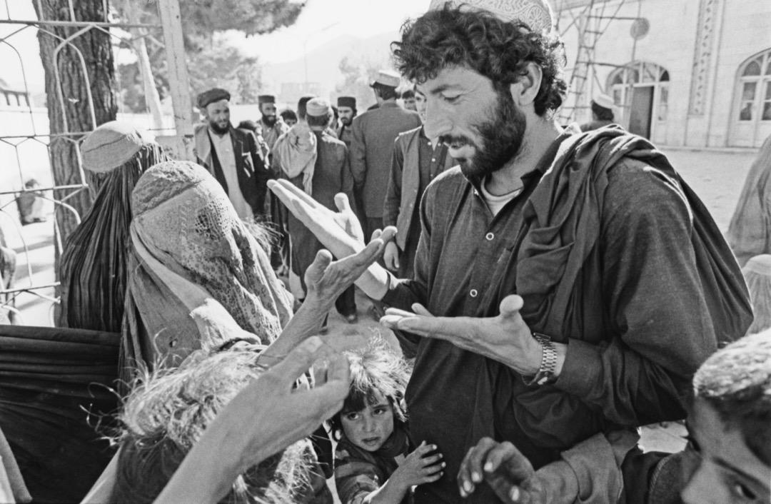 一名男子在阿富汗街頭與一名穿罩袍的女子對話。