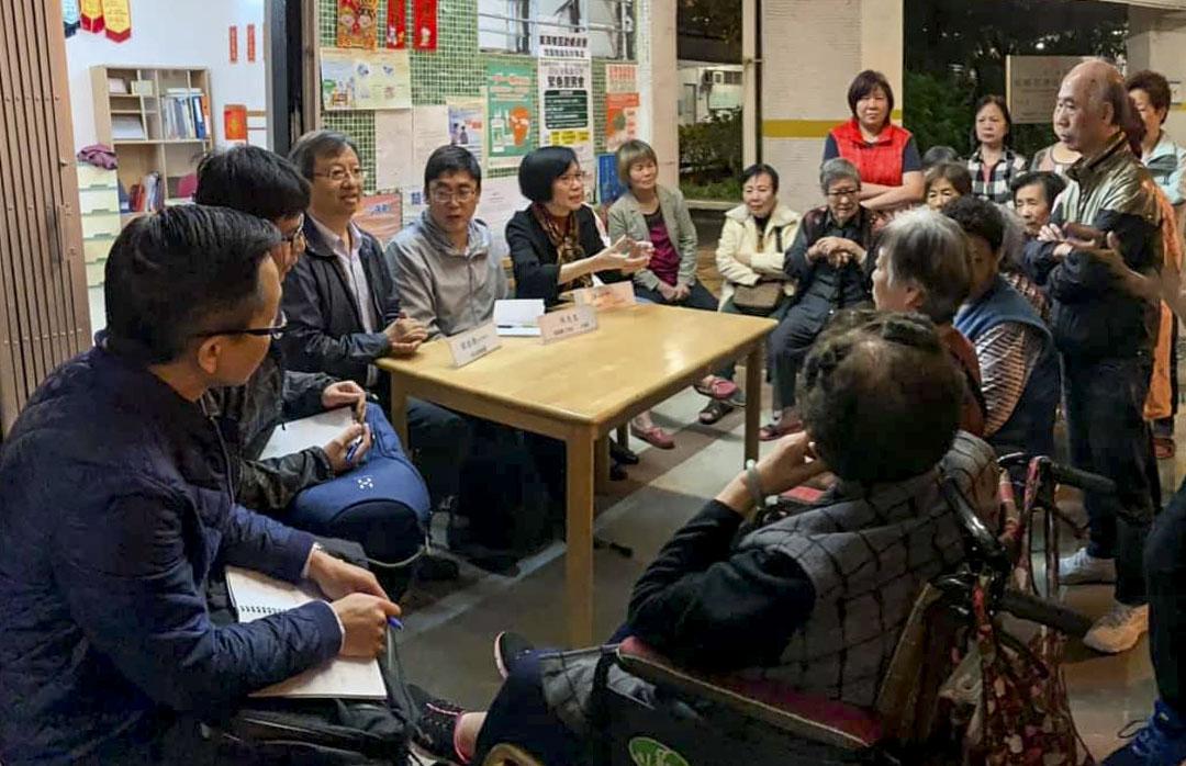 譚國僑於與街坊、房屋署工程師等人討論工程事宜。
