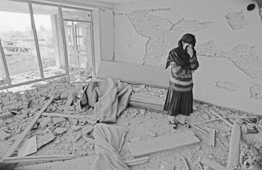 一名穿頭巾的女子站在一間破爛的房間裏。