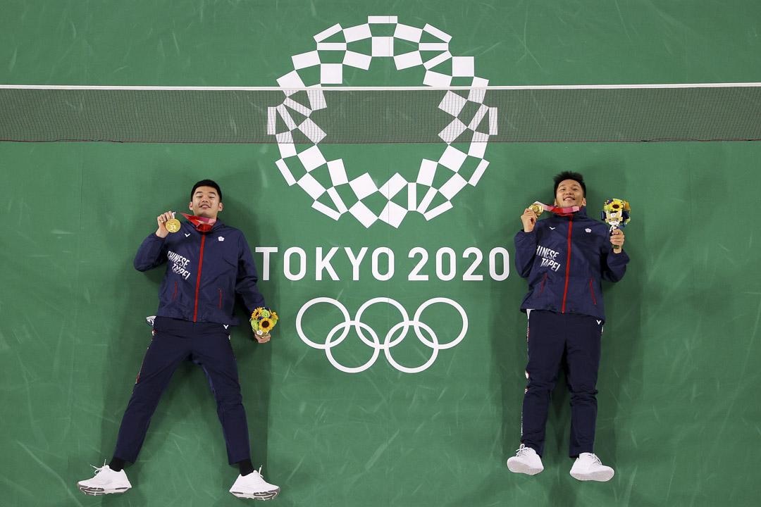 2021年7月31日,羽毛球男雙金牌得主台灣選手王齊麟、李洋在球場合影留念。