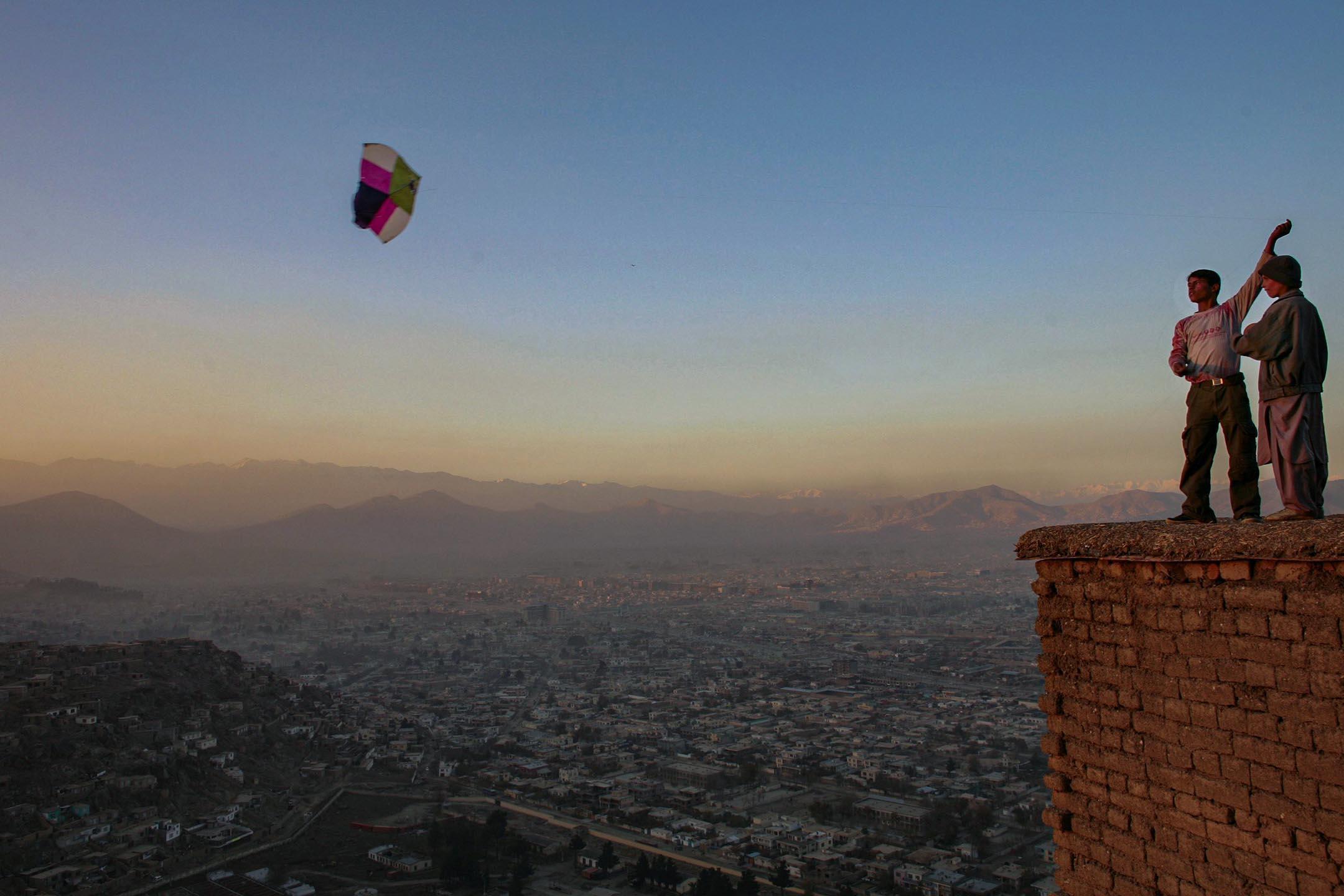 2006年11月23日阿富汗喀布爾,男孩在俯瞰喀布爾的山上放風箏。 攝:Paula Bronstein/Getty Images