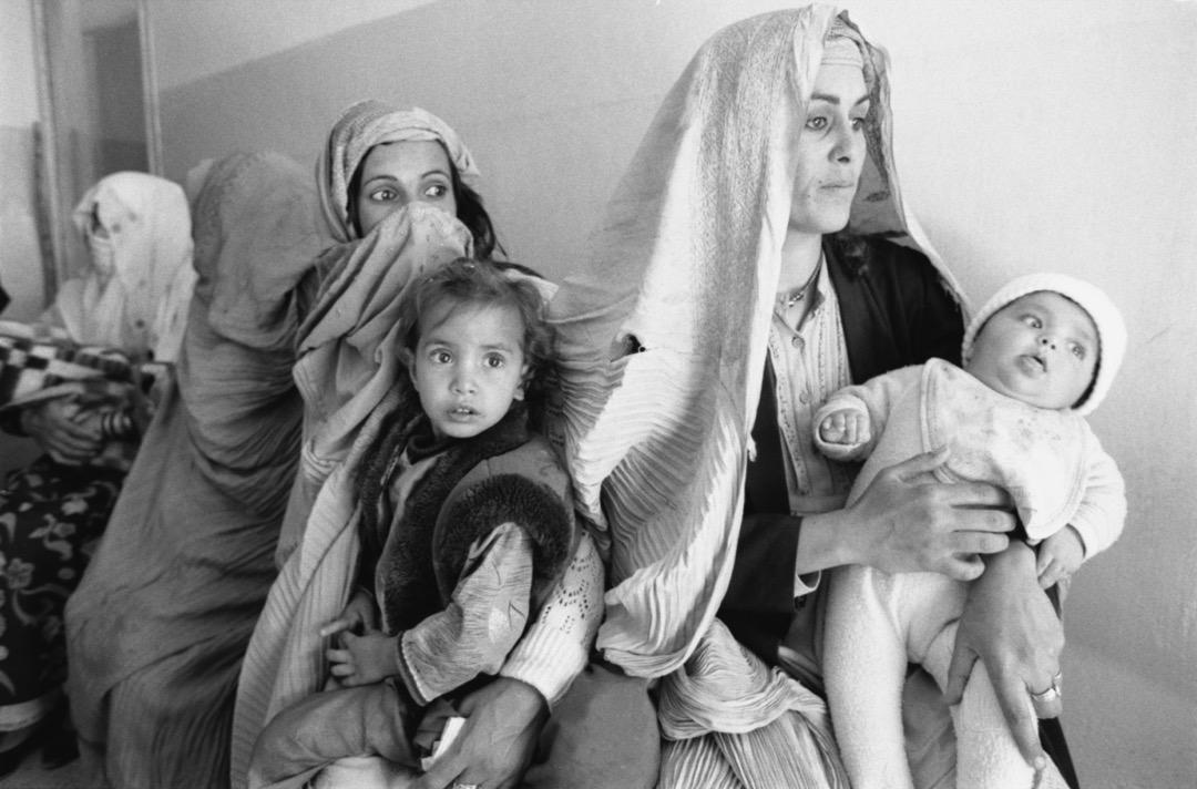 數名穿頭巾的女子抱著孩子等候醫療服務。