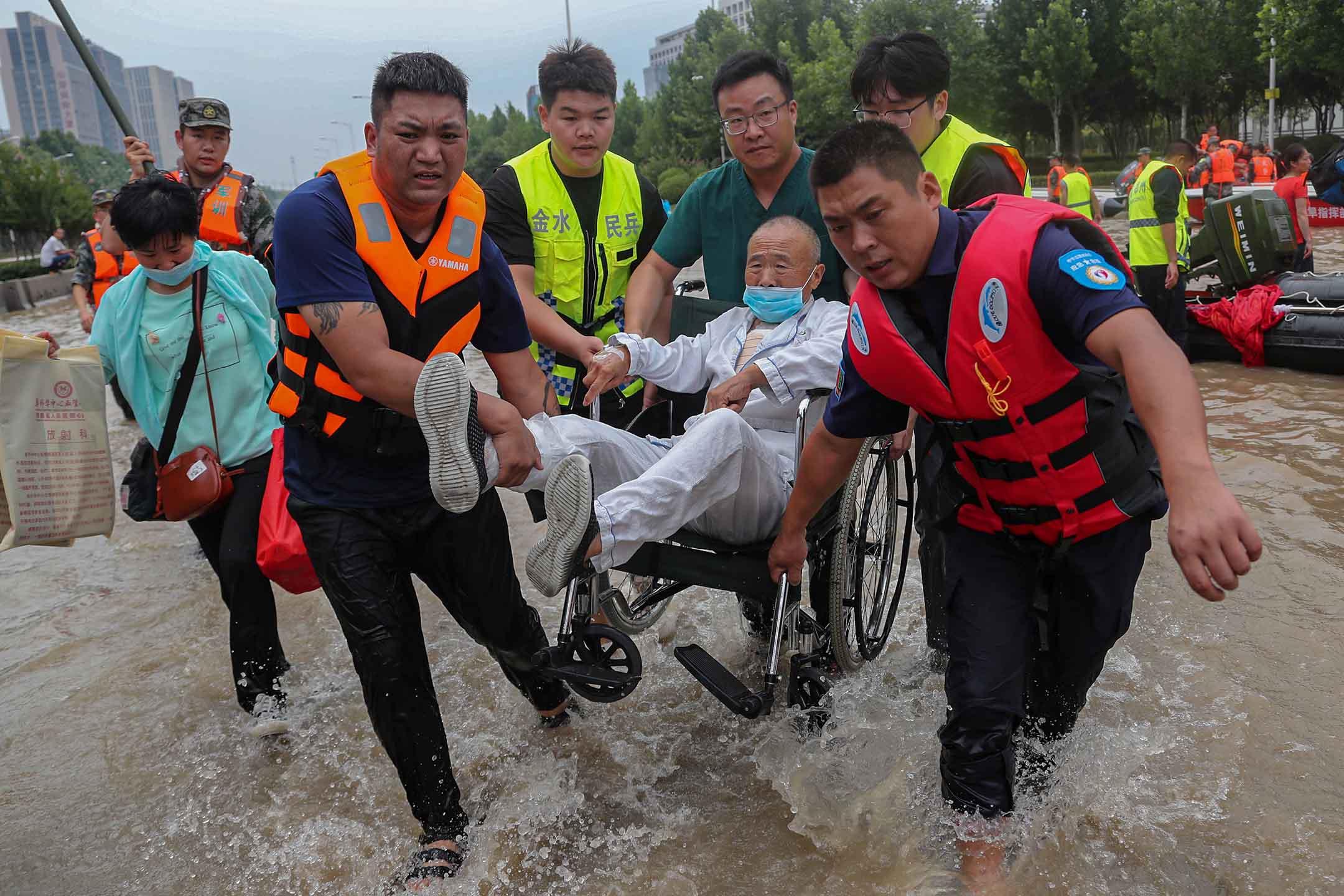 2021年7月22日中國河南省鄭州市,救援人員在醫院拯救一名坐在輪椅上的患者。