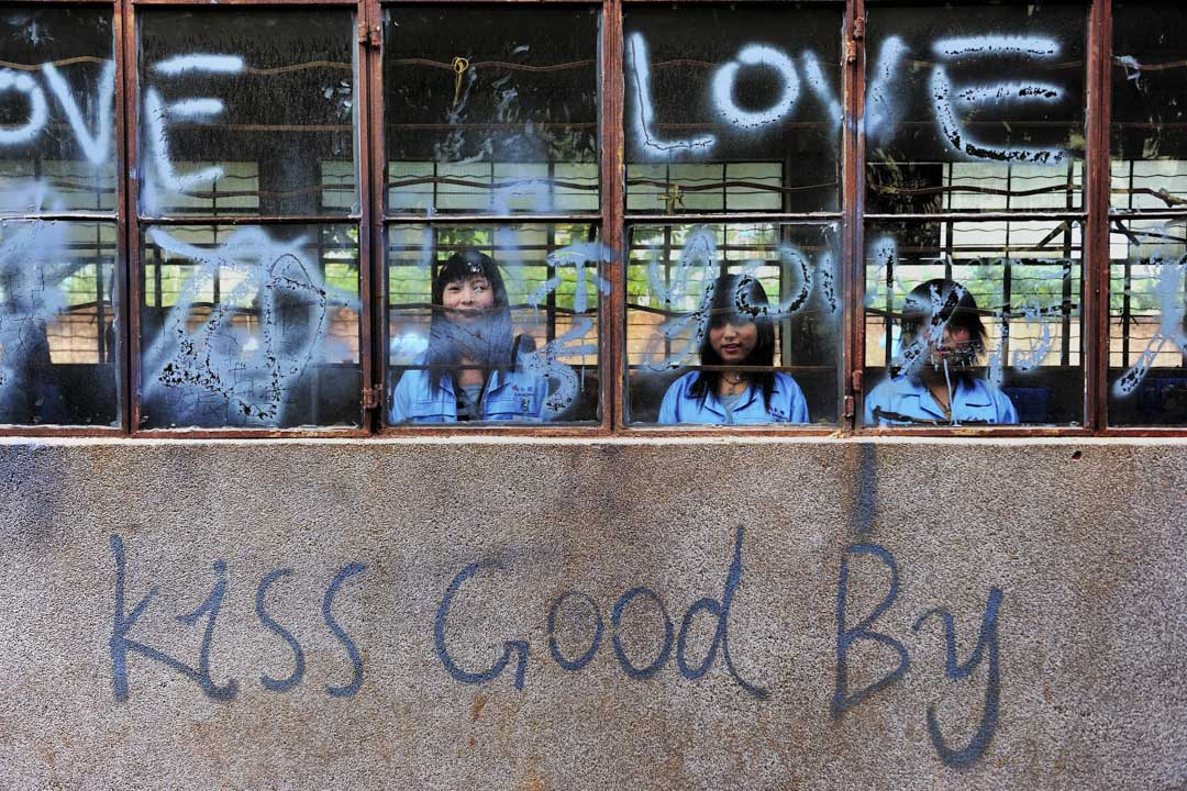 2009年3月9日,三名來自河南的18 歲工人在深圳一間人力資源公司等待工作。 攝:China Photos/Getty Images