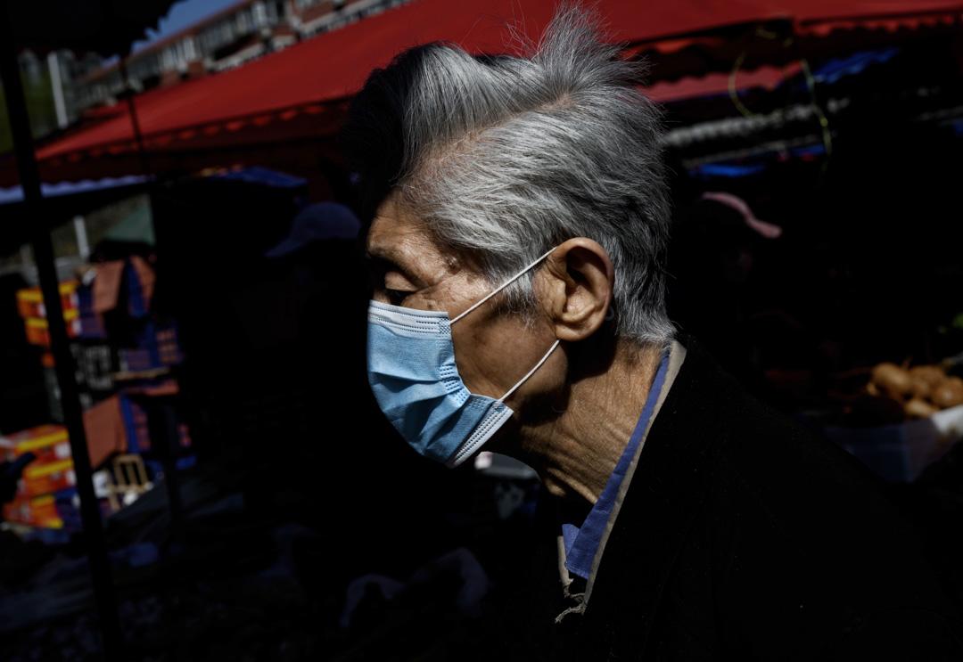 2020年4月3日,一名男士戴著口罩北京的一個戶外食品市場購物。