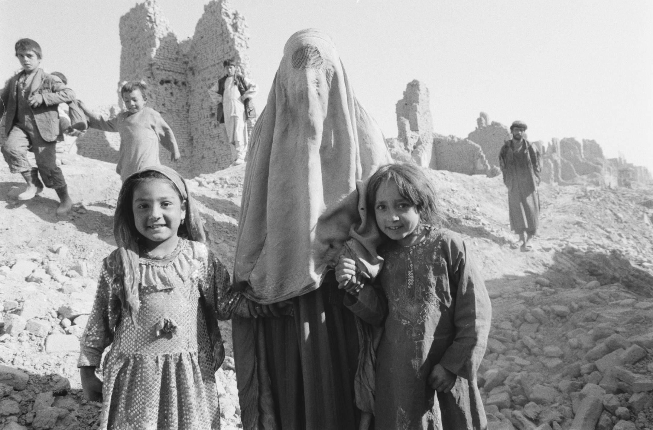阿富汗,一名穿罩袍的女子牽著另外兩名女孩的手,在瓦礫中合照。 攝:David Turnley/Corbis/VCG via Getty Images