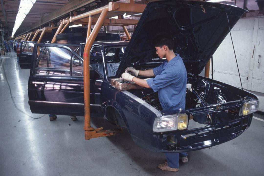 1992年,工人在上海大眾汽車的裝配廠上工作。