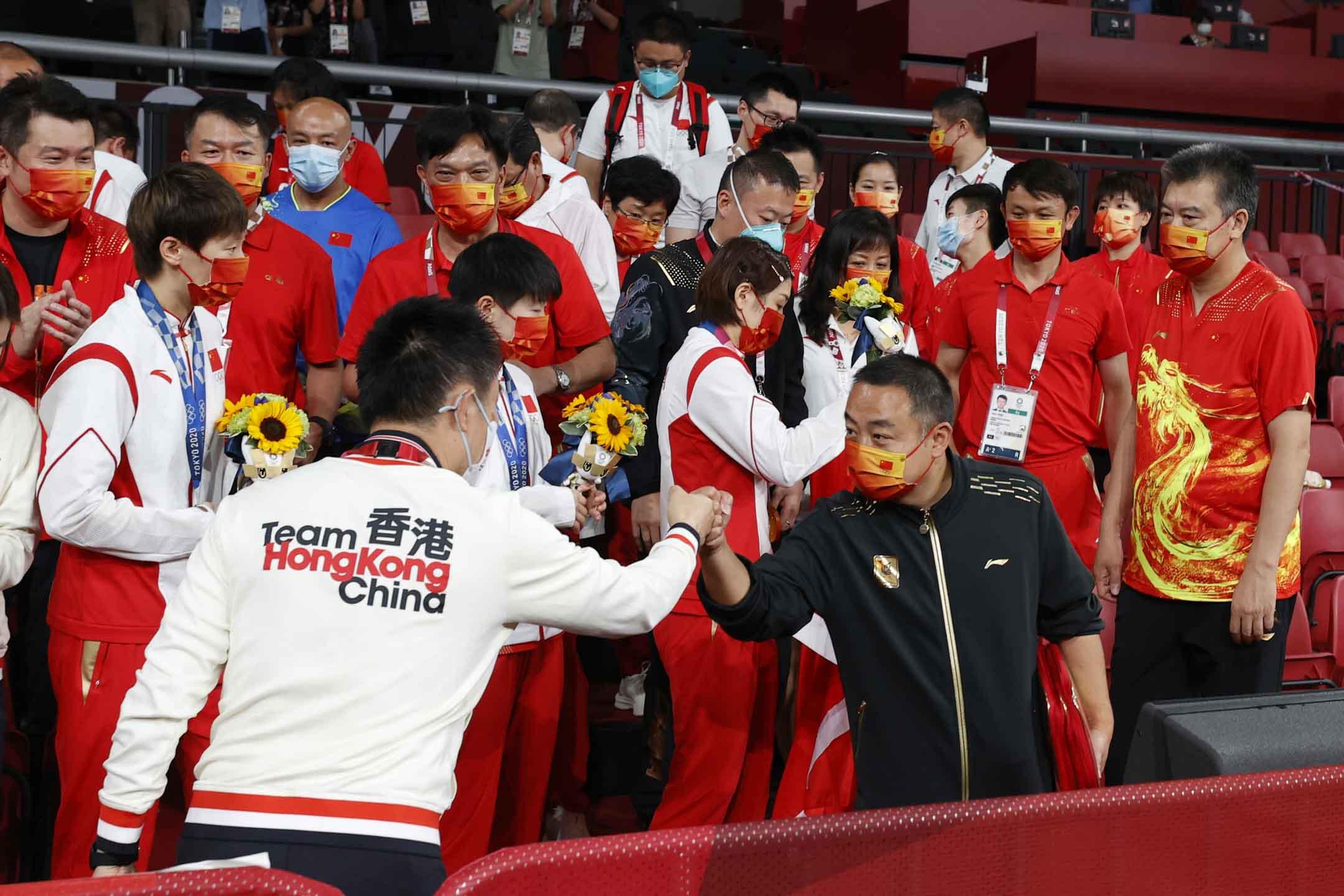 2021年8月5日,乒乓球女子團體金牌賽頒獎儀式後,中國隊主教練劉國樑帶領隊員與香港隊一起慶祝。 攝:Hai Handan/China News Service via Getty Images